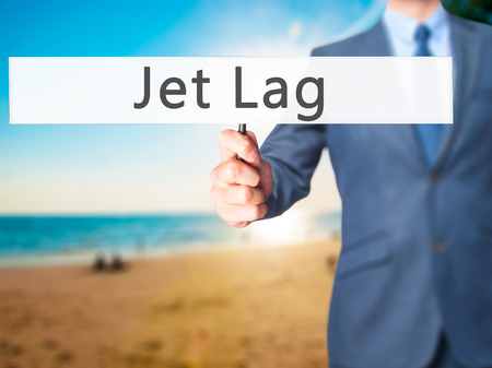 lag: Jet Lag - Businessman hand holding sign. Business, technology, internet concept. Stock Photo