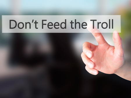 troublemaker: Dont Feed the Troll - Hand pressing a button on blurred background concept . Business, technology, internet concept. Stock Photo Stock Photo