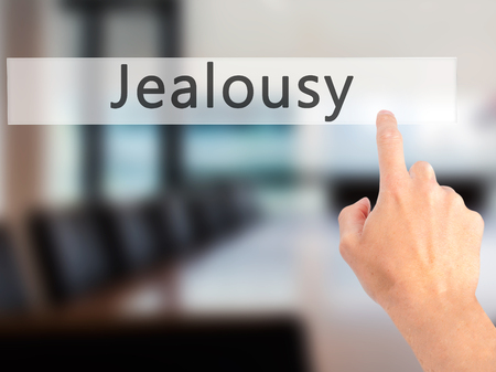 celos: Jealousy - Hand pressing a button on blurred background concept . Business, technology, internet concept. Stock Photo