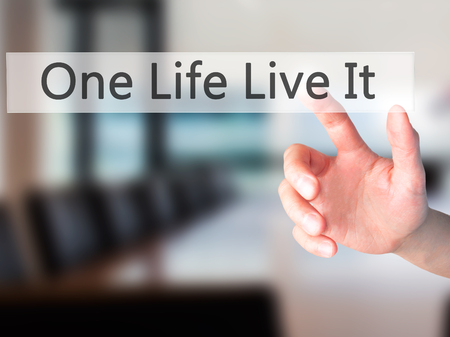 adrenaline rush: One Life Live It - Hand pressing a button on blurred background concept . Business, technology, internet concept. Stock Photo Stock Photo
