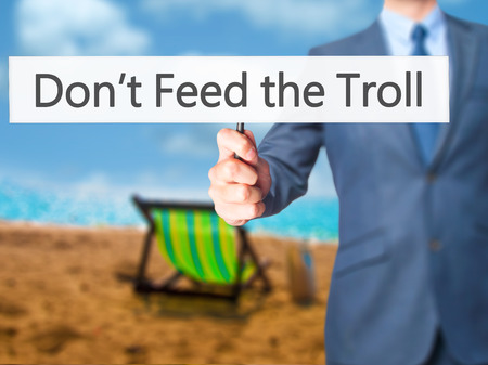 instigator: Dont Feed the Troll - Businessman hand holding sign. Business, technology, internet concept. Stock Photo Stock Photo