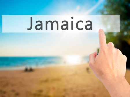 rastafari: Jamaica - Hand pressing a button on blurred background concept . Business, technology, internet concept. Stock Photo