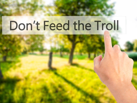 ludicrous: Dont Feed the Troll - Hand pressing a button on blurred background concept . Business, technology, internet concept. Stock Photo Stock Photo