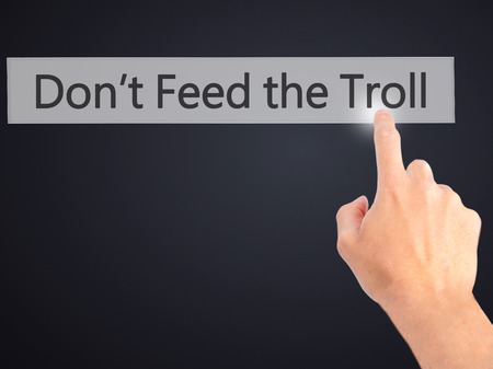 Dont Feed the Troll - Hand pressing a button on blurred background concept . Business, technology, internet concept. Stock Photo Stock Photo