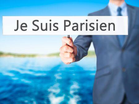 hand holding sign: Je Suis Parisien ( I am Parisien)  - Businessman hand holding sign. Business, technology, internet concept. Stock Photo