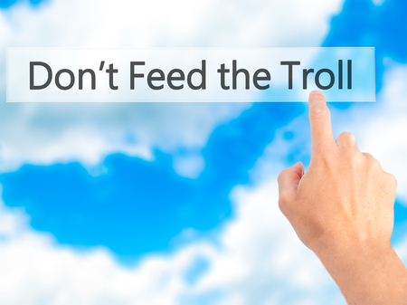 sarcastic: Dont Feed the Troll - Hand pressing a button on blurred background concept . Business, technology, internet concept. Stock Photo Stock Photo