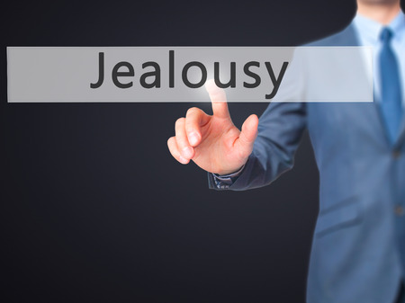 celos: Los celos - Mano de empresario botón en la interfaz de pantalla táctil de prensado. Negocios, la tecnología, el concepto de internet. Foto de stock