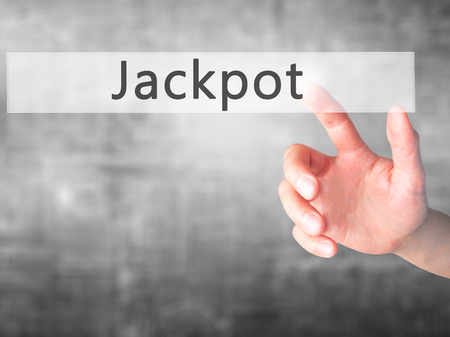 Jackpot - Hand pressing a button on blurred background concept . Business, technology, internet concept. Stock Photo
