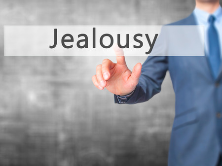 envious: Jealousy - Businessman hand pressing button on touch screen interface. Business, technology, internet concept. Stock Photo