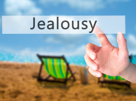 jealousy: Jealousy - Hand pressing a button on blurred background concept . Business, technology, internet concept. Stock Photo