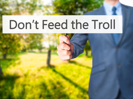 sarcastic: Dont Feed the Troll - Businessman hand holding sign. Business, technology, internet concept. Stock Photo Stock Photo