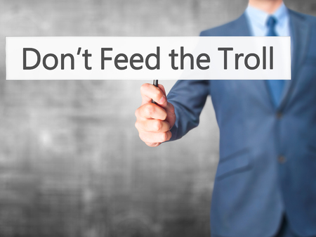 ludicrous: Dont Feed the Troll - Businessman hand holding sign. Business, technology, internet concept. Stock Photo Stock Photo