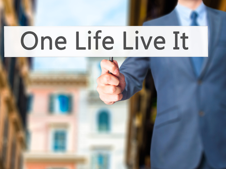 adrenaline rush: One Life Live It - Businessman hand holding sign. Business, technology, internet concept. Stock Photo