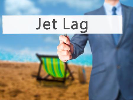 lag: Jet Lag - Businessman hand holding sign. Business, technology, internet concept. Stock Photo