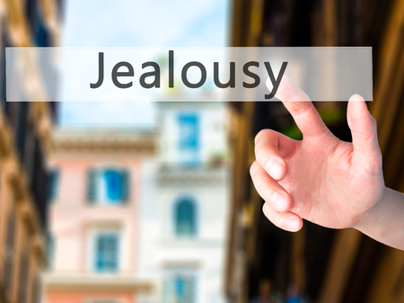 envious: Jealousy - Hand pressing a button on blurred background concept . Business, technology, internet concept. Stock Photo