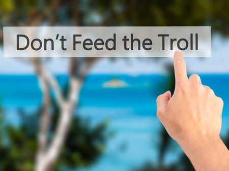 instigator: Dont Feed the Troll - Hand pressing a button on blurred background concept . Business, technology, internet concept. Stock Photo Stock Photo