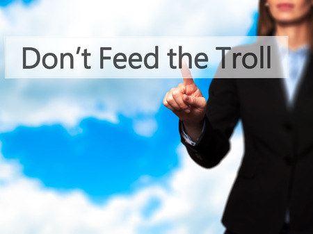 trolling: Dont Feed the Troll - Businesswoman hand pressing button on touch screen interface. Business, technology, internet concept. Stock Photo