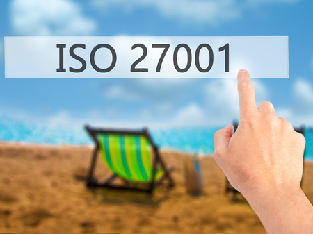 certify: ISO 27001 - Hand pressing a button on blurred background concept . Business, technology, internet concept. Stock Photo Stock Photo