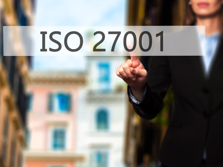 certify: ISO 27001 - Businesswoman hand pressing button on touch screen interface. Business, technology, internet concept. Stock Photo