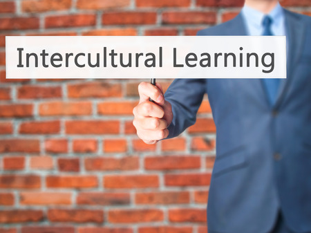 intercultural: Intercultural Learning - Businessman hand holding sign. Business, technology, internet concept. Stock Photo