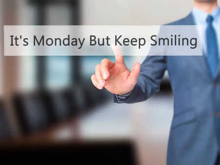 plausible: Its Monday But Keep Smiling  - Businessman hand pressing button on touch screen interface. Business, technology, internet concept. Stock Photo