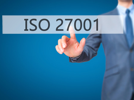 standardization: ISO 27001 - Businessman hand pressing button on touch screen interface. Business, technology, internet concept. Stock Photo
