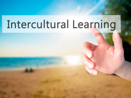 intercultural: Intercultural Learning - Hand pressing a button on blurred background concept . Business, technology, internet concept. Stock Photo Stock Photo