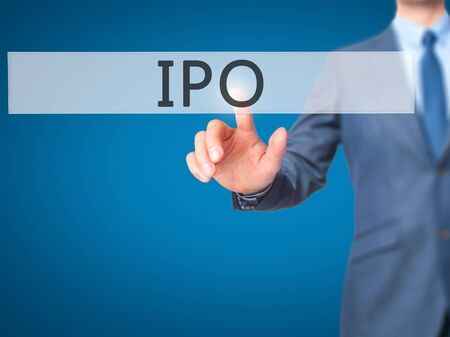 IPO - Businessman hand pressing button on touch screen interface. Business, technology, internet concept. Stock Photo