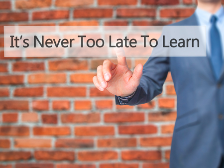 too late: Its Never Too Late To Learn - Businessman hand pressing button on touch screen interface. Business, technology, internet concept. Stock Photo