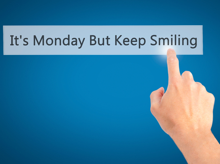 plausible: Its Monday But Keep Smiling  - Hand pressing a button on blurred background concept . Business, technology, internet concept. Stock Photo