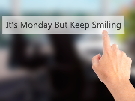 Its Monday But Keep Smiling  - Hand pressing a button on blurred background concept . Business, technology, internet concept. Stock Photo
