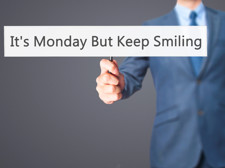 plausible: Its Monday But Keep Smiling  - Businessman hand holding sign. Business, technology, internet concept. Stock Photo Stock Photo