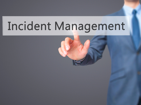 Incident Management - Businessman hand pressing button on touch screen interface. Business, technology, internet concept. Stock Photo