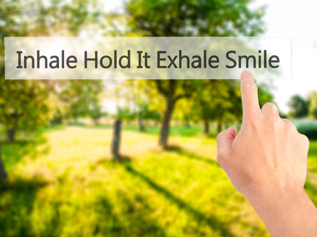 artistic addiction: Inhale Hold It Exhale Smile - Hand pressing a button on blurred background concept . Business, technology, internet concept. Stock Photo Stock Photo