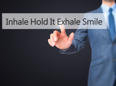 to inhale: Inhale Hold It Exhale Smile - Businessman hand pressing button on touch screen interface. Business, technology, internet concept. Stock Photo