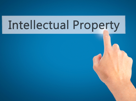 infringement: Intellectual Property - Hand pressing a button on blurred background concept . Business, technology, internet concept. Stock Photo Stock Photo