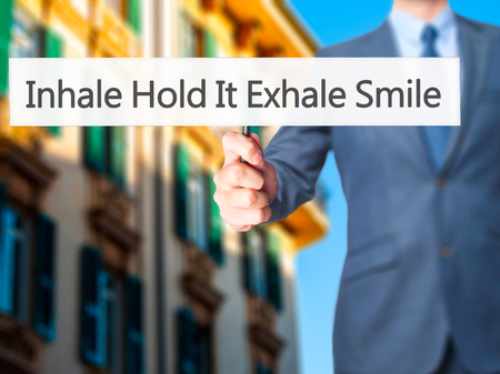 to inhale: Inhale Hold It Exhale Smile - Businessman hand holding sign. Business, technology, internet concept. Stock Photo Stock Photo