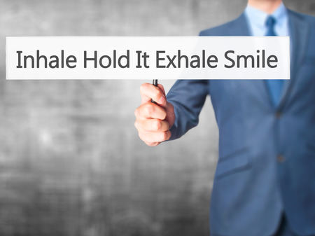 exhale: Inhale Hold It Exhale Smile - Businessman hand holding sign. Business, technology, internet concept. Stock Photo Stock Photo