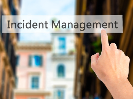 incident: Incident Management - Hand pressing a button on blurred background concept . Business, technology, internet concept. Stock Photo