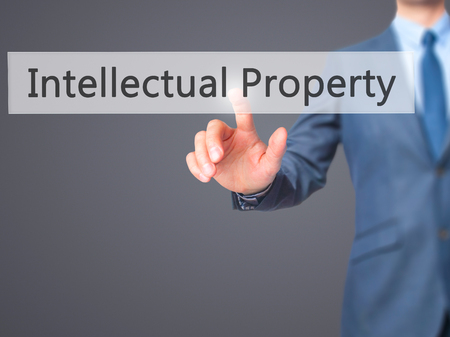 infringement: Intellectual Property - Businessman hand pressing button on touch screen interface. Business, technology, internet concept. Stock Photo