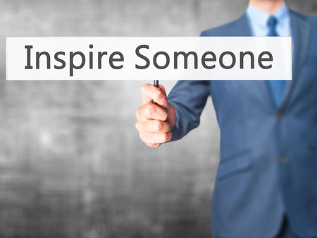 someone: Inspire Someone - Businessman hand holding sign. Business, technology, internet concept. Stock Photo