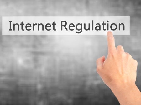 company secrets: Internet Regulation - Hand pressing a button on blurred background concept . Business, technology, internet concept. Stock Photo