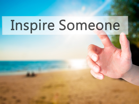 someone: Inspire Someone - Hand pressing a button on blurred background concept . Business, technology, internet concept. Stock Photo