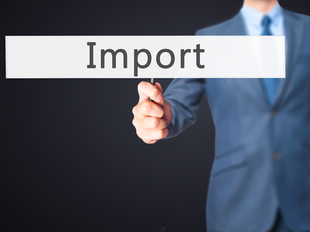importation: Import - Businessman hand holding sign. Business, technology, internet concept. Stock Photo