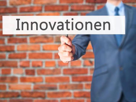 innovator: Innovationen (Innovationin German) - Businessman hand holding sign. Business, technology, internet concept. Stock Photo Stock Photo