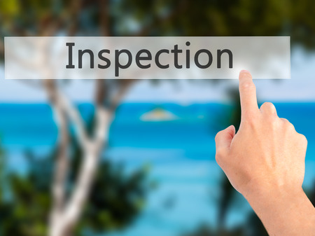 warranty questions: Inspection - Hand pressing a button on blurred background concept . Business, technology, internet concept. Stock Photo