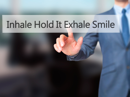 exhale: Inhale Hold It Exhale Smile - Businessman hand pressing button on touch screen interface. Business, technology, internet concept. Stock Photo