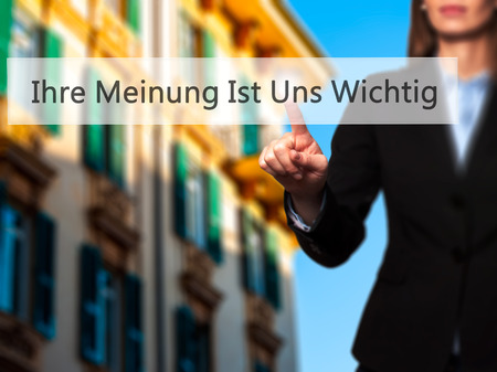 wichtig: Ihre Meinung Ist Uns Wichtig! (Your Opinion is Important to Us in German) - Businesswoman hand pressing button on touch screen interface. Business, technology, internet concept. Stock Photo