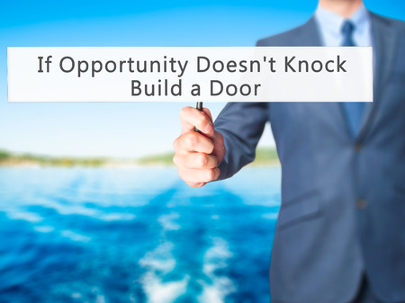 knock on door: If Opportunity Doesnt Knock Build a Door - Businessman hand holding sign. Business, technology, internet concept. Stock Photo