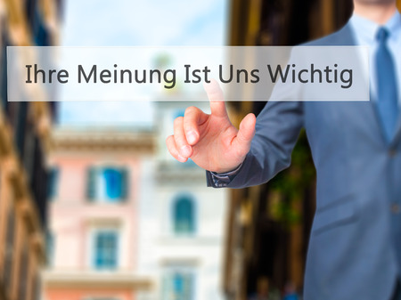 wichtig: Ihre Meinung Ist Uns Wichtig! (Your Opinion is Important to Us in German) - Businessman hand pressing button on touch screen interface. Business, technology, internet concept. Stock Photo Stock Photo